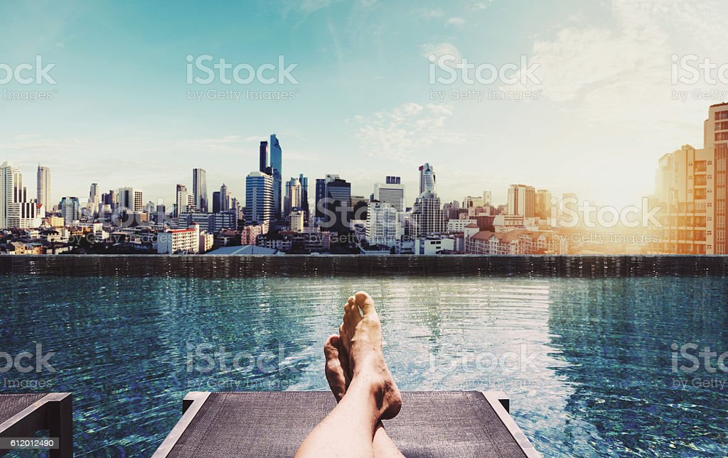 Relaxing in holidays, Panoramic a guy relaxing at swimming pool stock photo