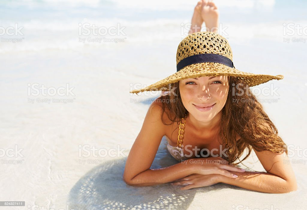 Portrait of a beautiful young woman lying in the sun on the beach