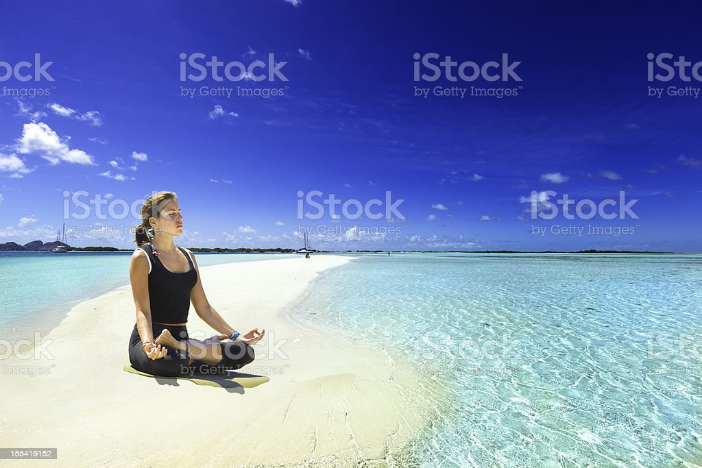 Relaxing in yoga lotus pose on tropical turquoise beach island royalty-free stock photo