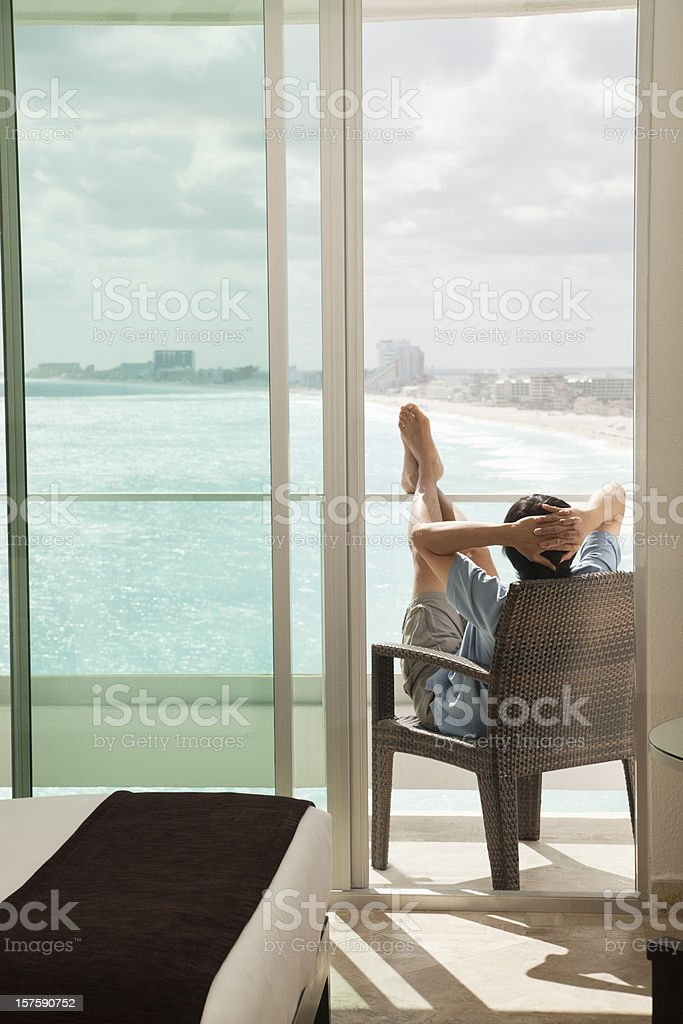 Relaxing Man on Hotel Room Balcony Enjoying Sea Beach View stock photo