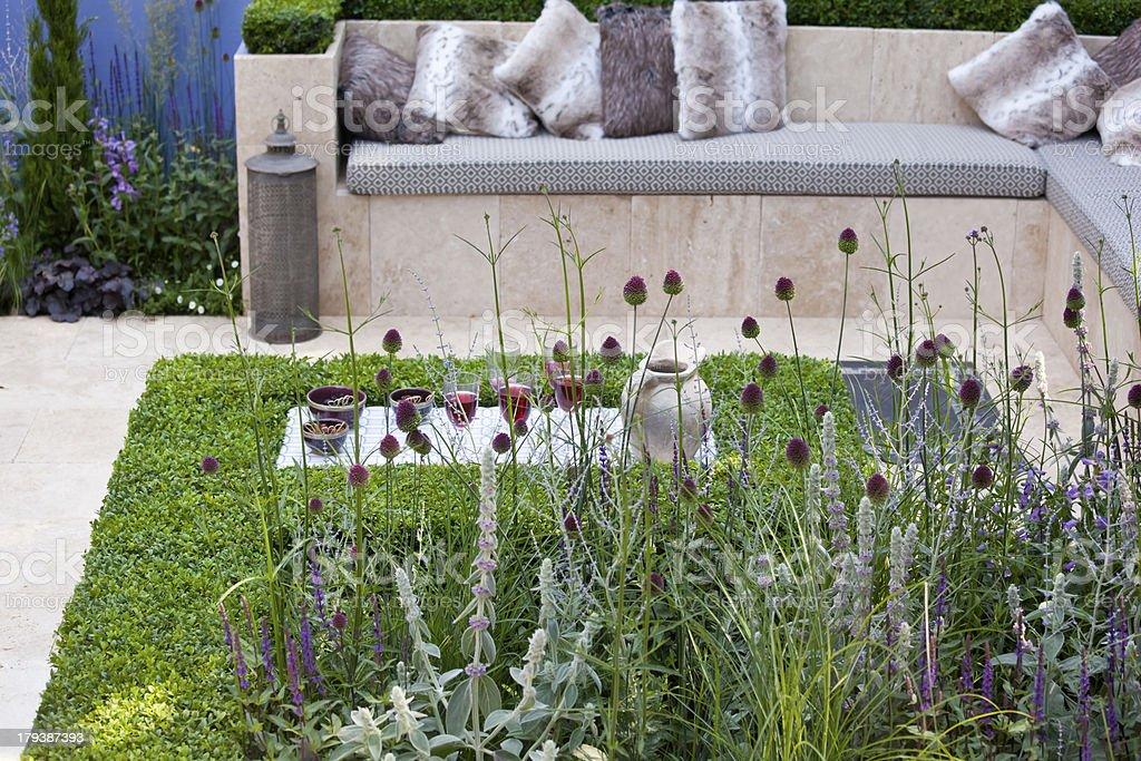 A contemporary, sunken Mediterranean garden made with terrazzo tiles...