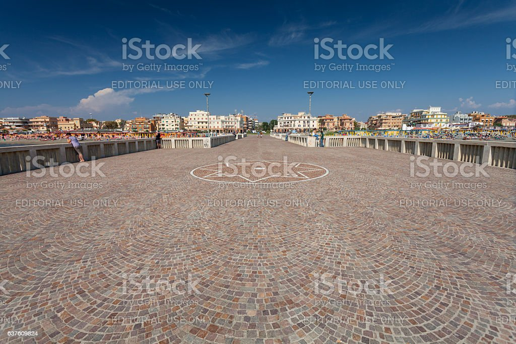 Relaxing people on the pier  near beautiful beach, Italy. stock photo
