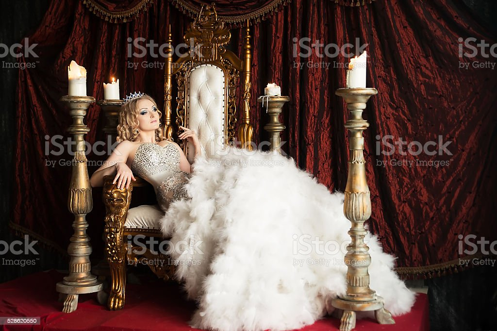 Relaxing queen on the throne. Joy, pleasure. Royal stock photo