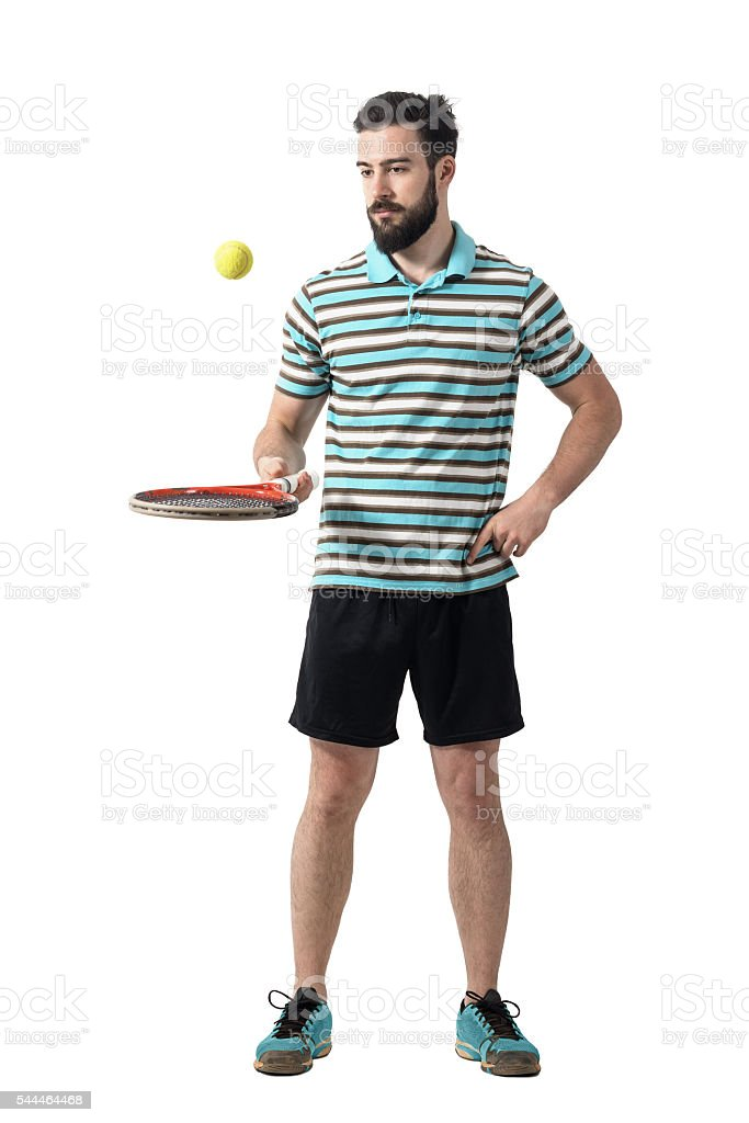 Relaxing tennis player in polo shirt bouncing ball with racket. stock photo