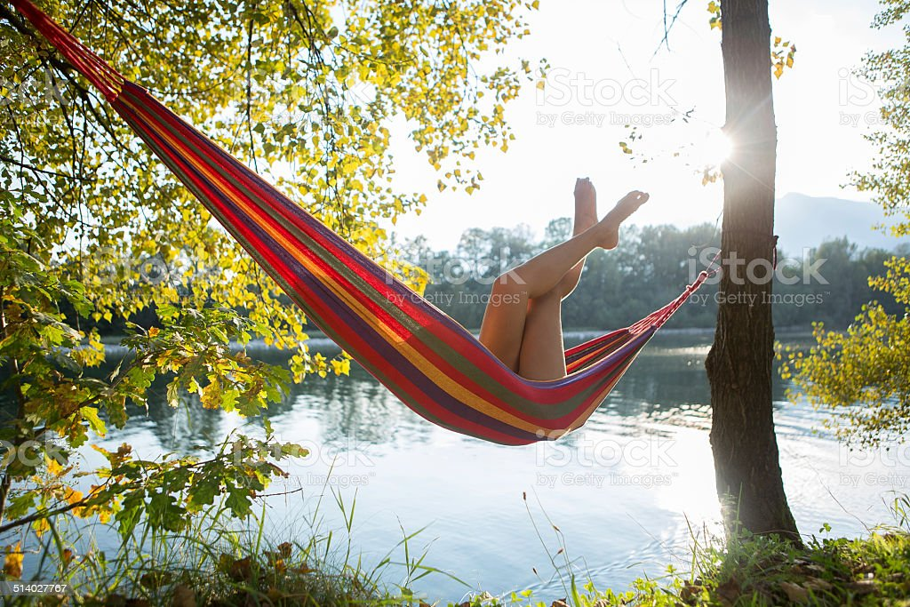 Relaxing time on hammock by the river at sunset stock photo