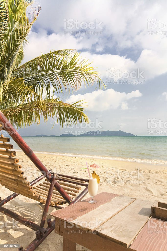 Relaxing under a palm trees with cocktail on loneliness beach royalty-free stock photo