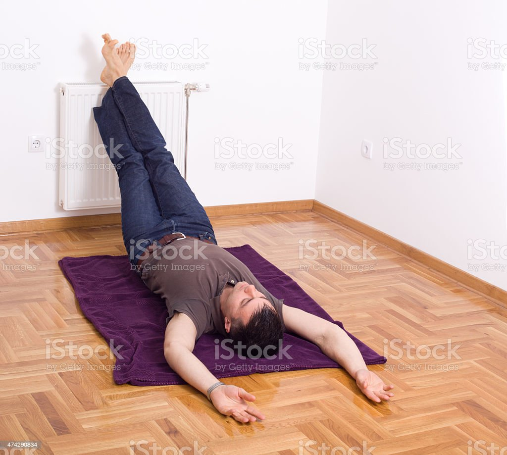 Relaxing with legs on the wall stock photo