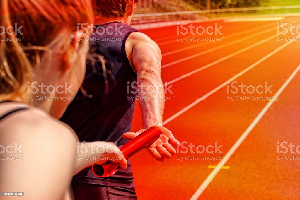Relay race handing over female male stock photo
