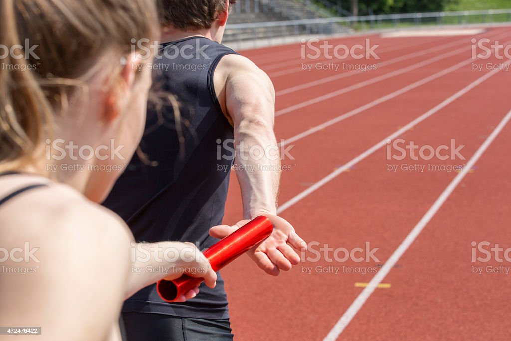 A relay race handing over the baton to a male runner stock photo