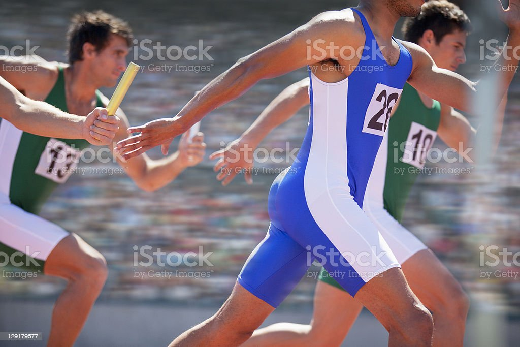 Relay race, male athletes passing relay baton stock photo