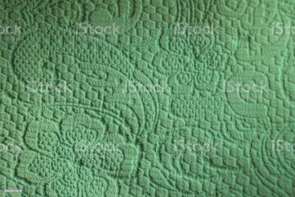 Relief squiggles and flowers on the turquoise fabric stock photo