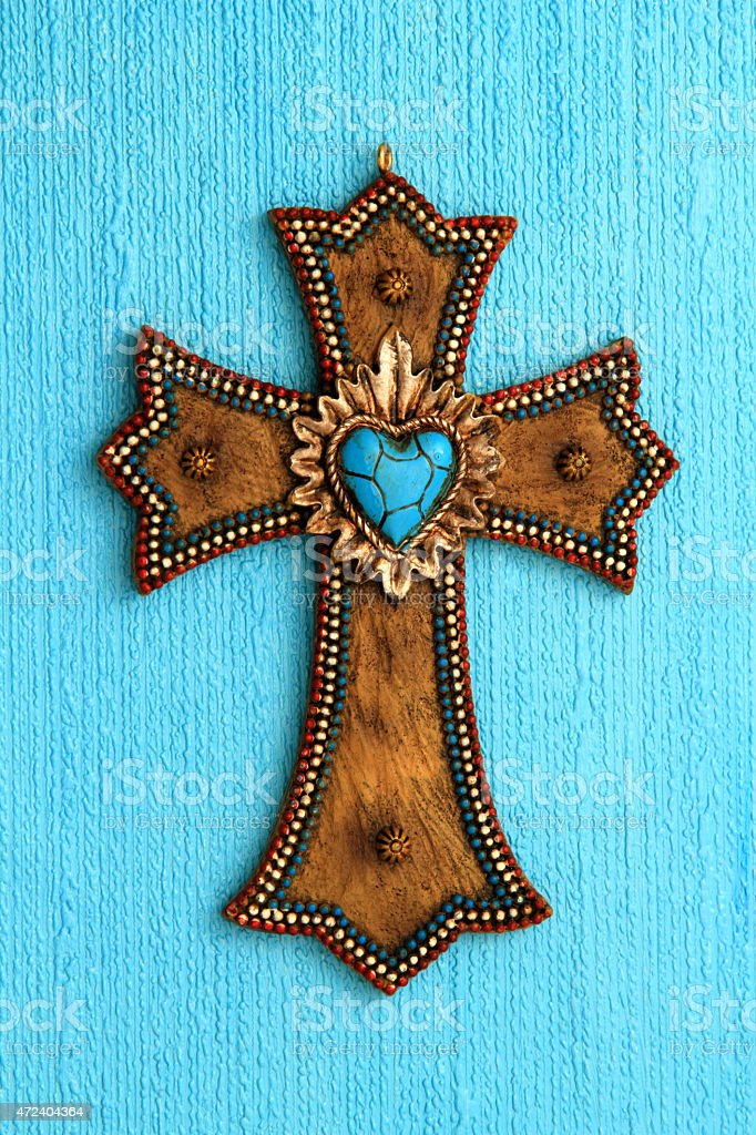 Religion: Brown Cross with turquoise heart and beaded edges stock photo