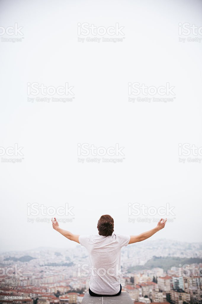 Religion - Young adult arms raised with urban scene stock photo