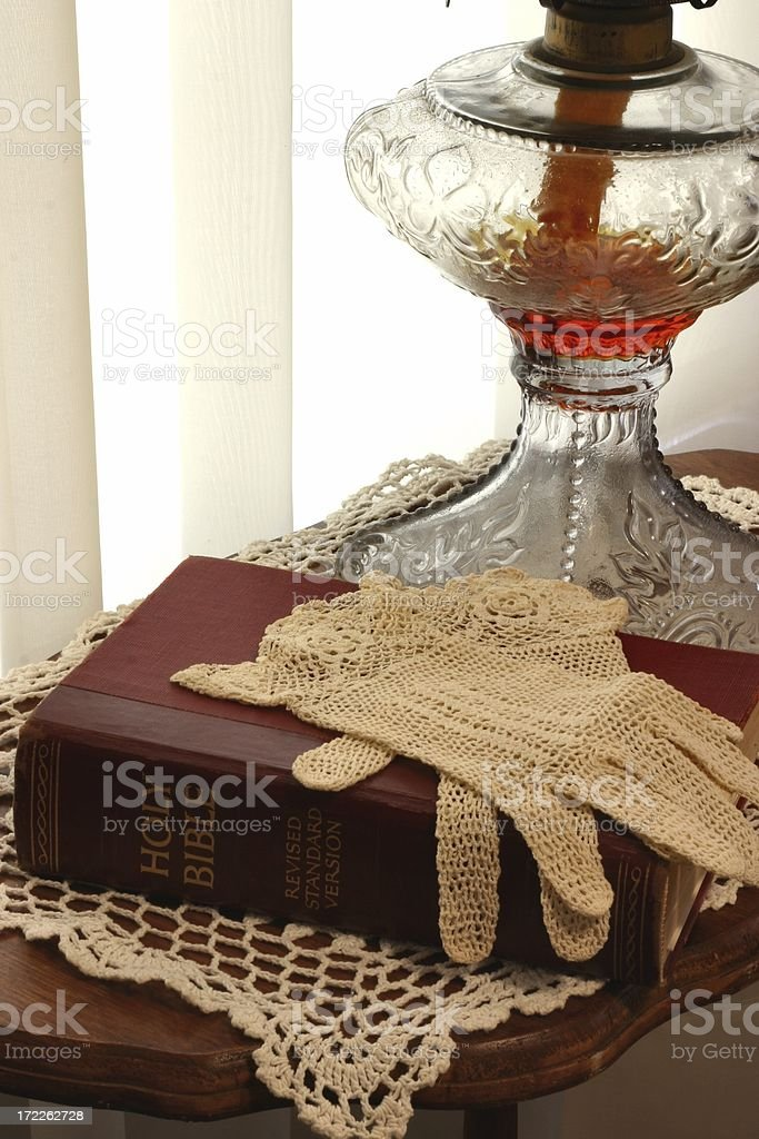 Religious: Antique Lamp with Bible & crocheted Gloves royalty-free stock photo