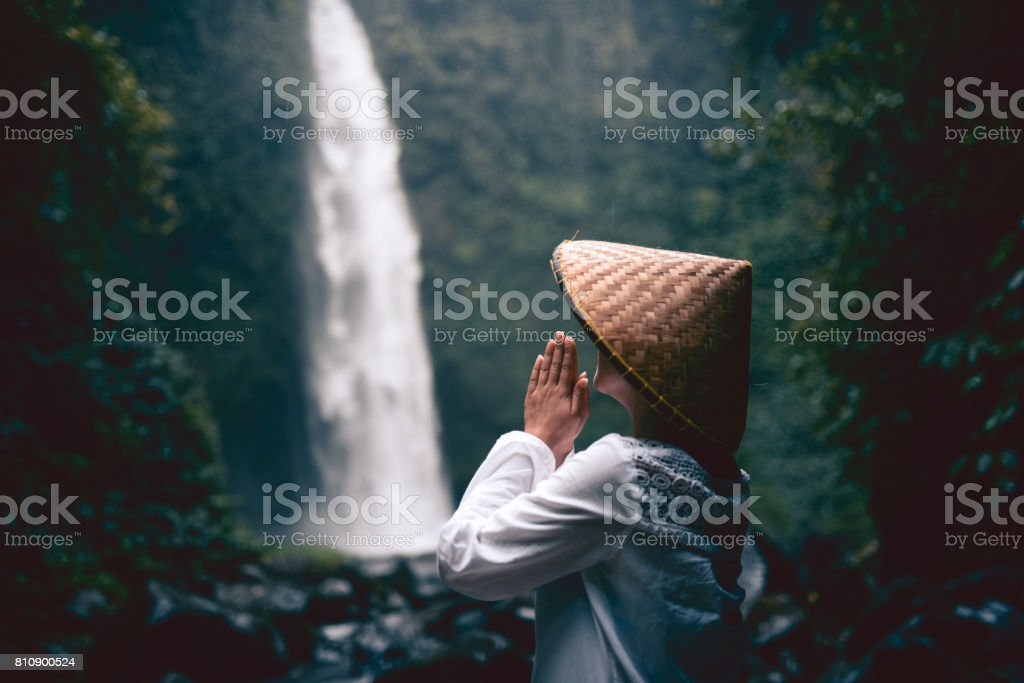 Religious Asian Female Praying by the Rainforest Waterfall stock photo