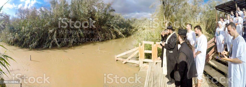 YERICHO, ISRAEL - 20 FEB, 2017: Religious christians with white clothes going into the water of the Jordan river at baptismal site Qasr el Yahud near Yericho stock photo
