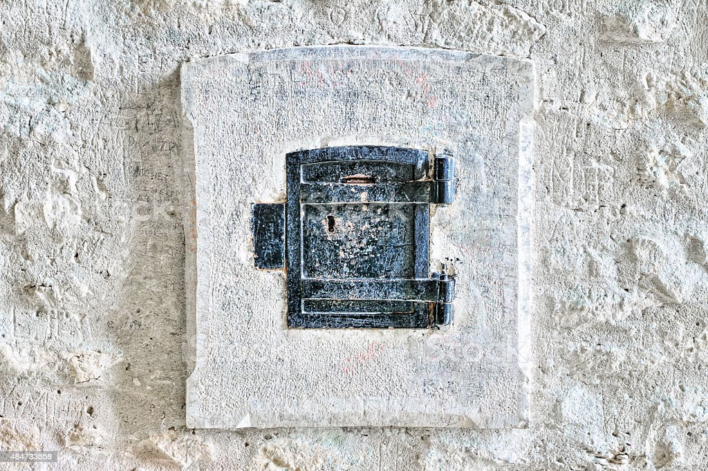 Religious closed box on old french chapel stone wall stock photo