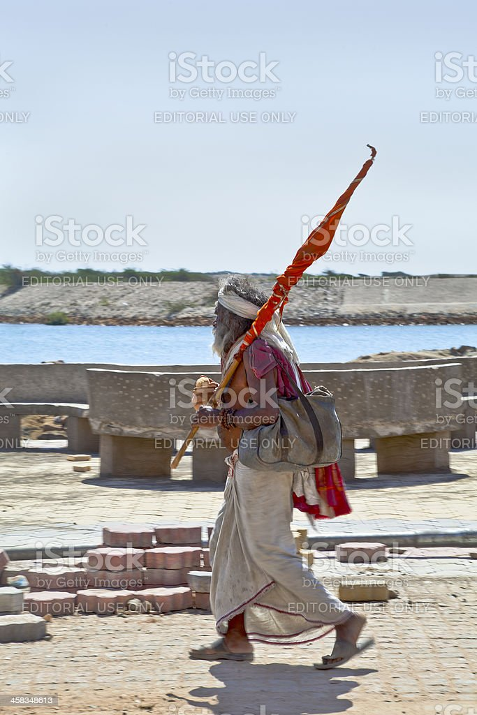 Religious Hindu man walking carrying a flag stock photo