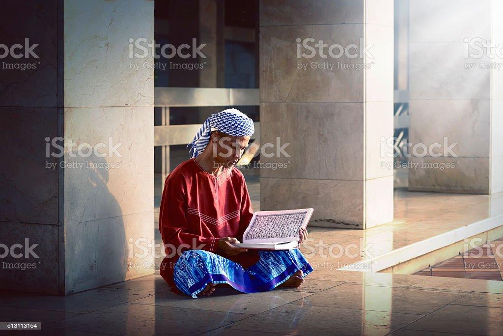 Religious muslim man reading holy koran stock photo