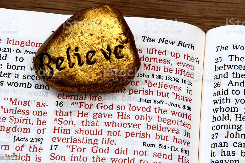 Religious: open Bible Scripture of John 3:16 with Believe stone stock photo