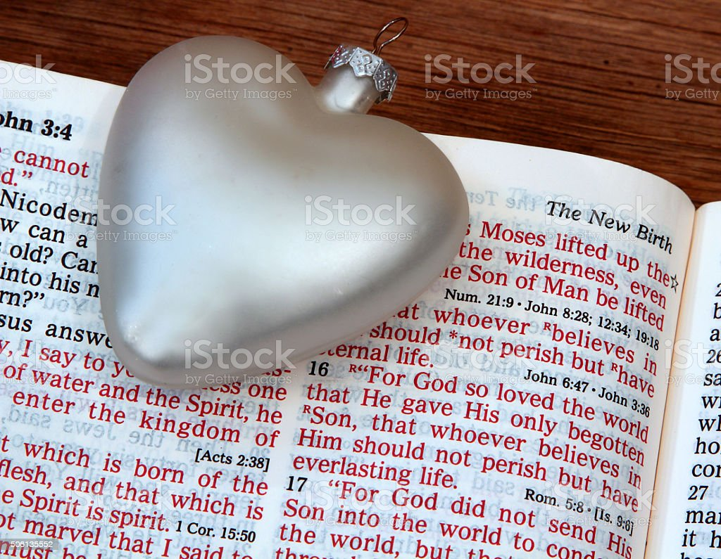 Religious: open Bible Scripture of John 3:16 with white heart stock photo