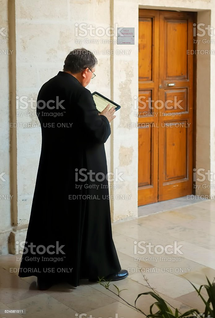 religious prays reading from a digital tablet stock photo