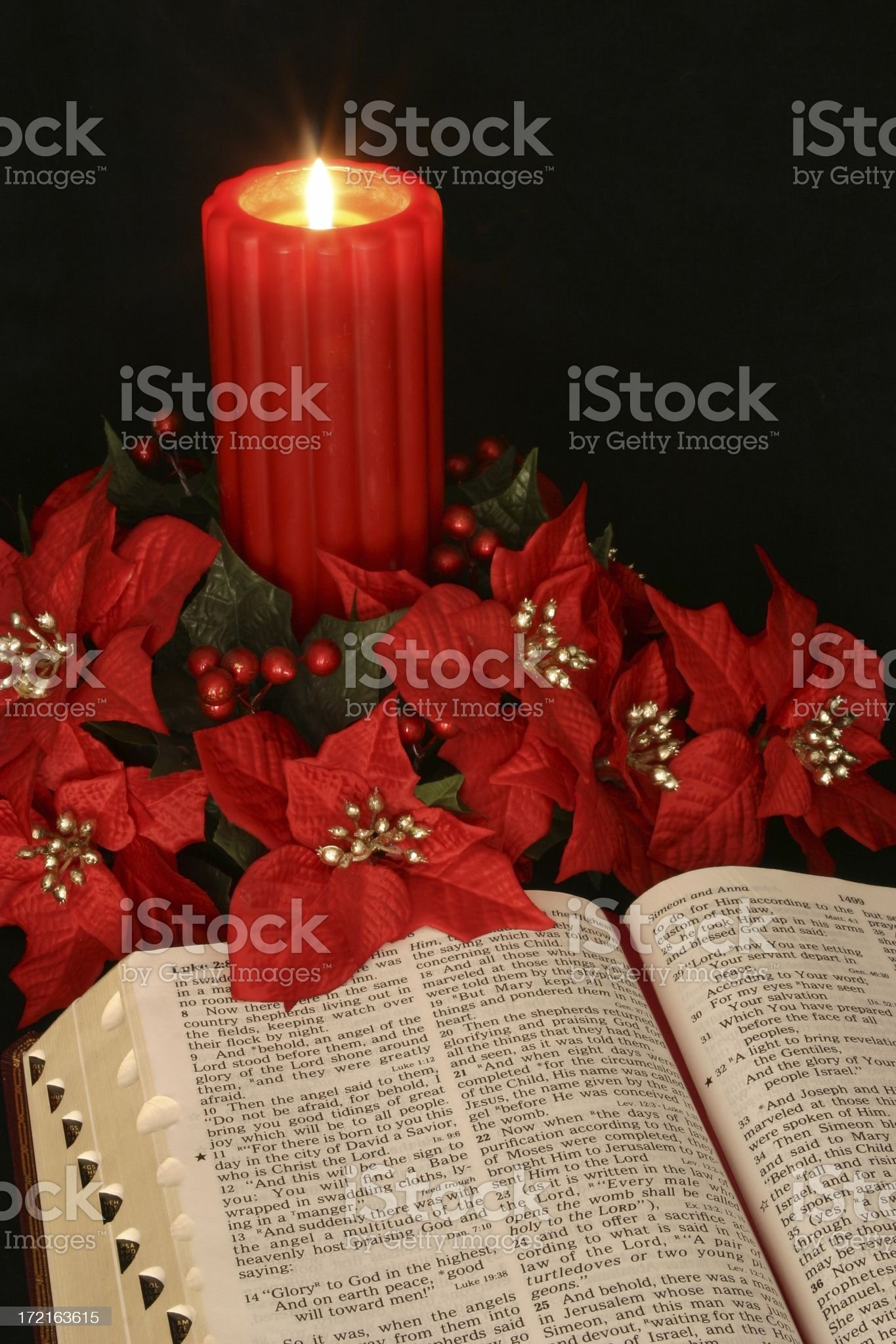 Religious: red Christmas Candle & open Bible with poinsettias royalty-free stock photo