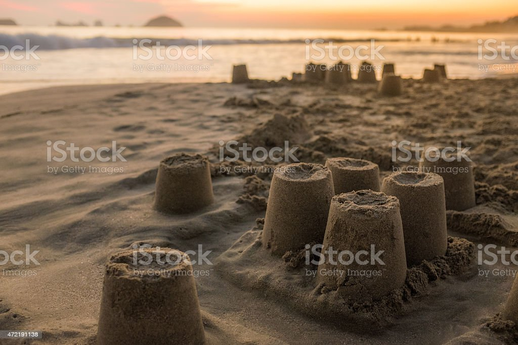 Remains of a sand castle at sunset stock photo