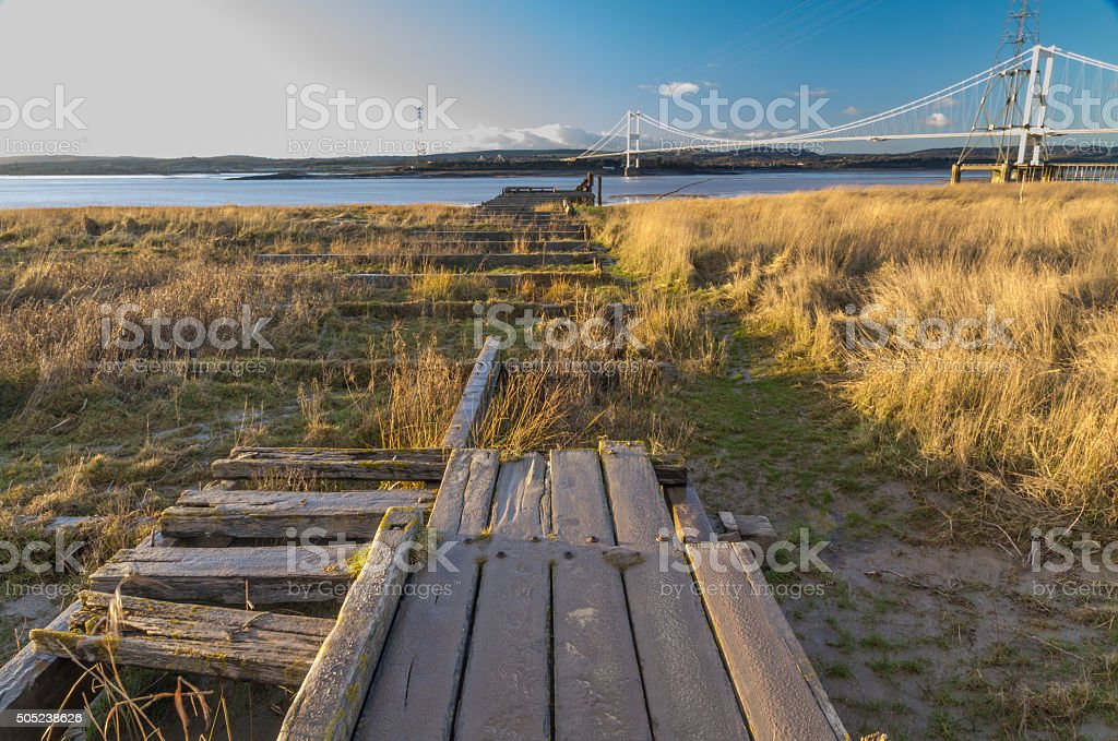 Remains of Aust Ferry pier with Severn Bridge in distance stock photo