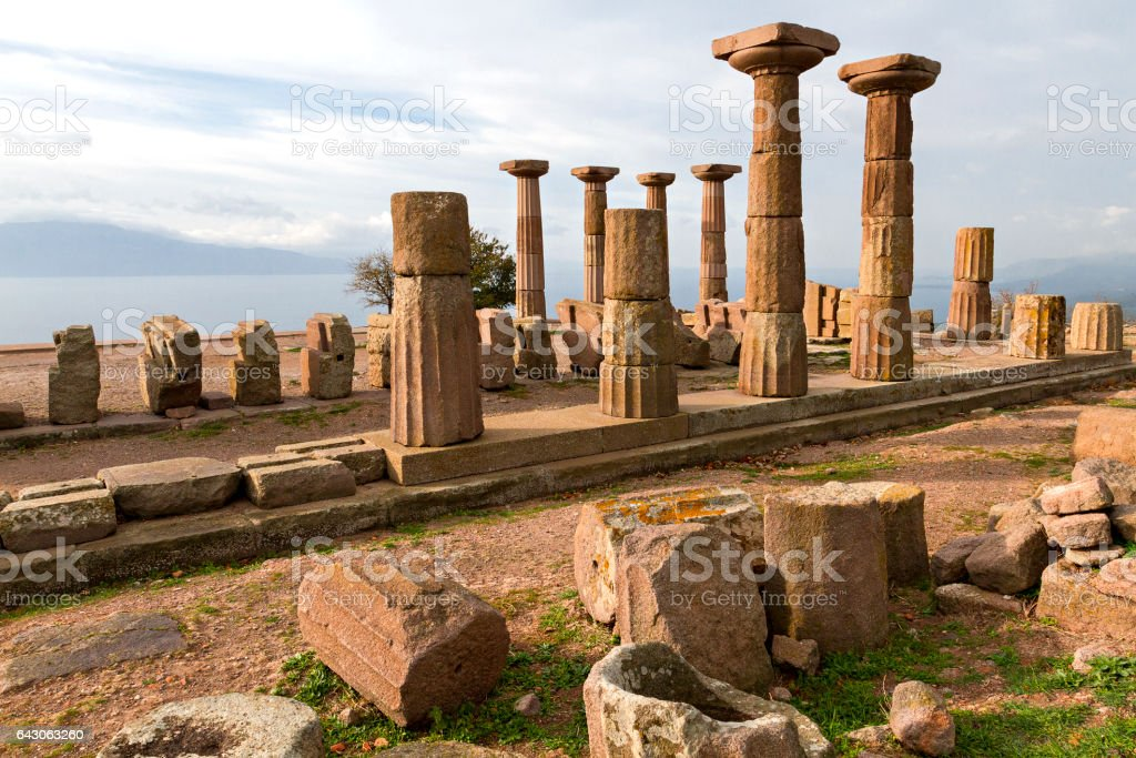 Remains of the Temple of Athena in the ancient site of Assos with the Greek Island Lesbos in silhouette, in the background, Turkey. stock photo
