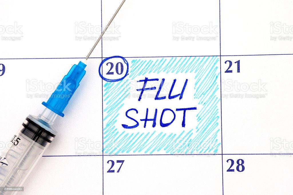 Reminder Flu Shot in calendar with syringe stock photo