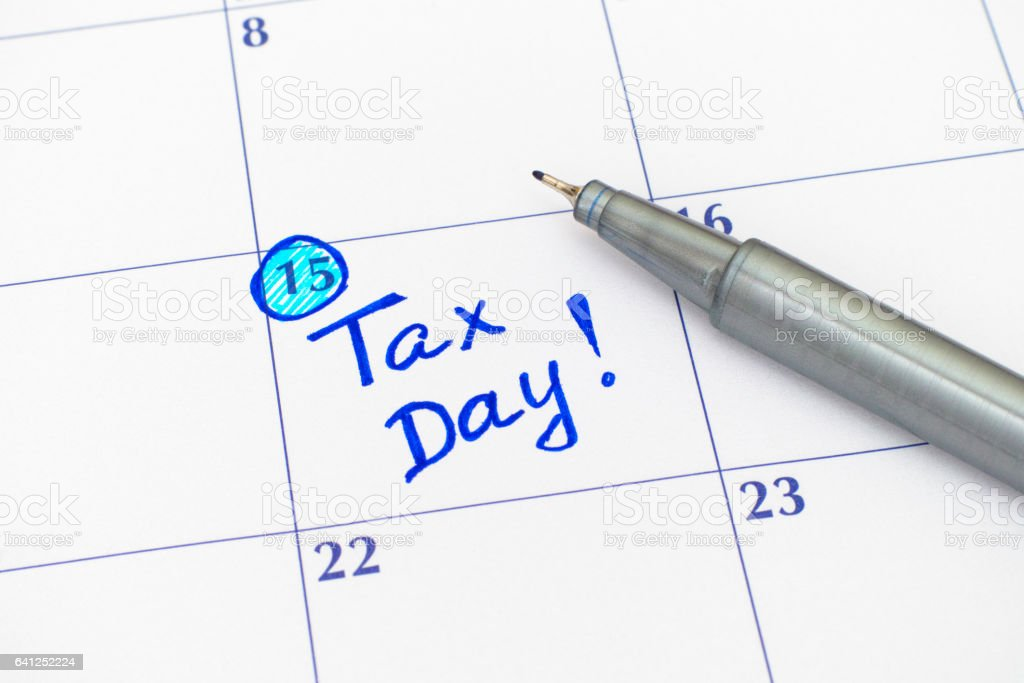 Reminder Tax day in calendar with blue pen stock photo