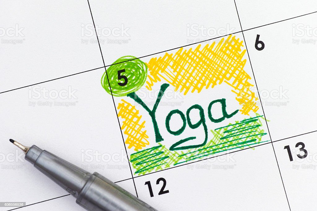 Reminder Yoga in calendar with pen stock photo