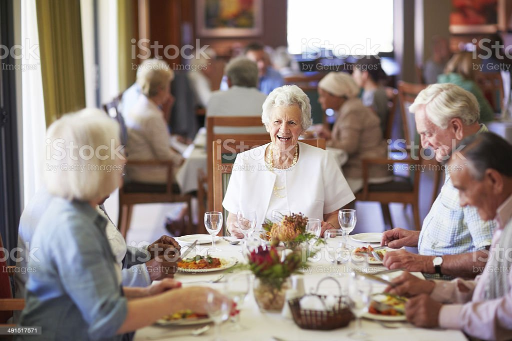 Reminiscing with friends at the dining table stock photo