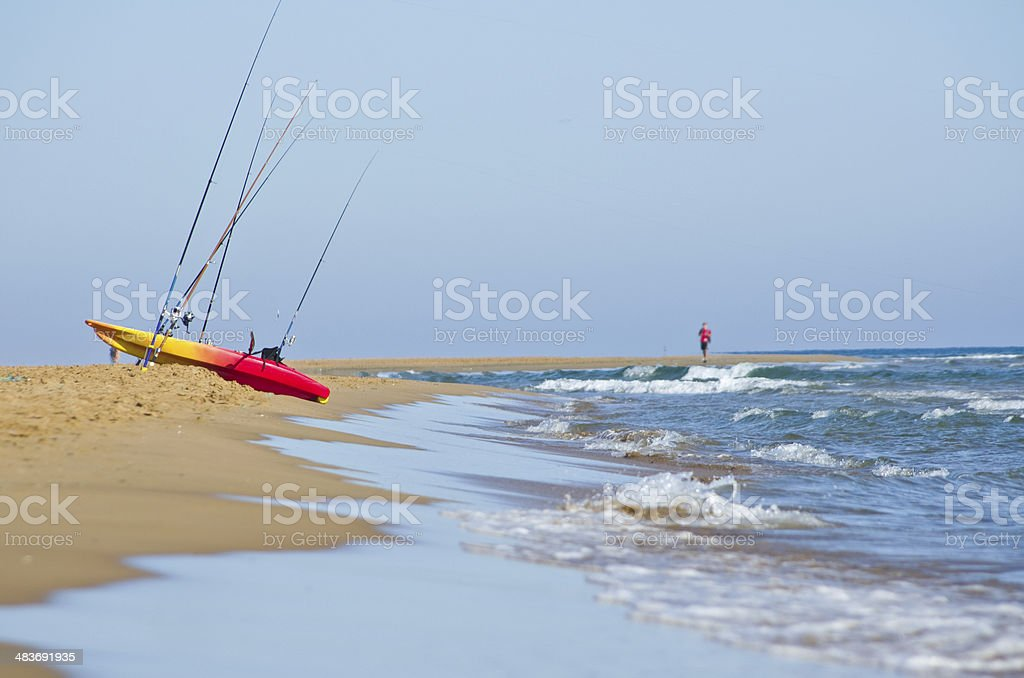 Remote beach scene with kayak and fishing rods royalty-free stock photo