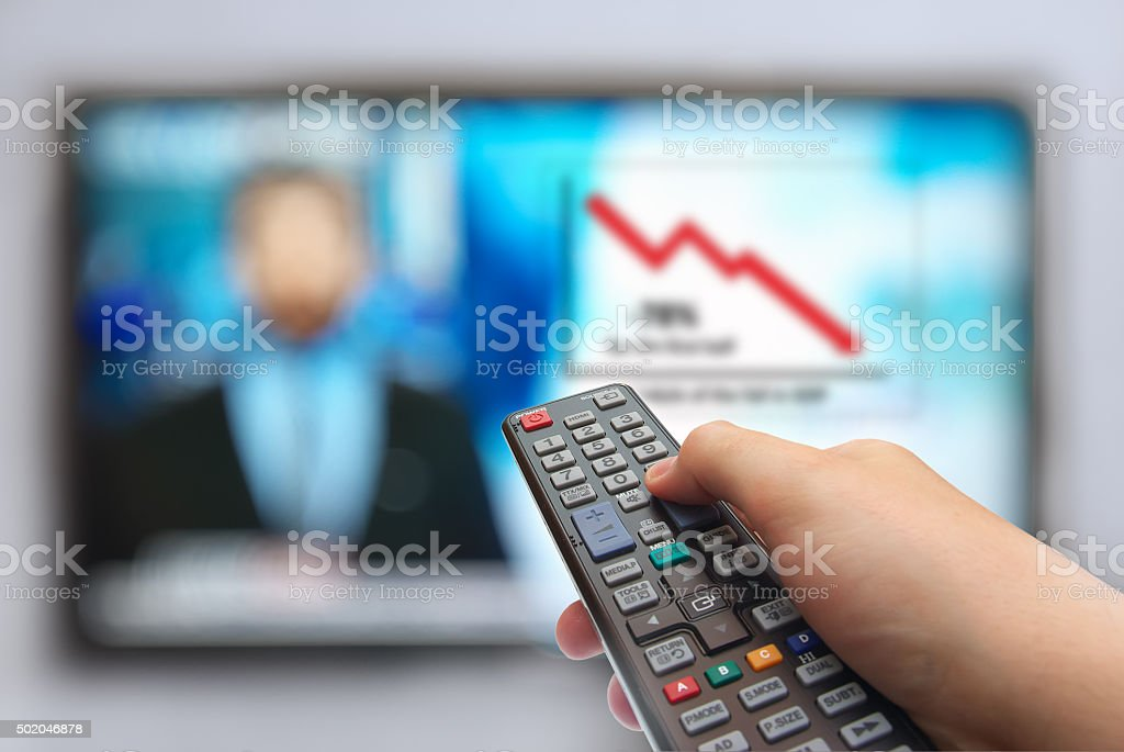 remote control in hand and TV stock photo