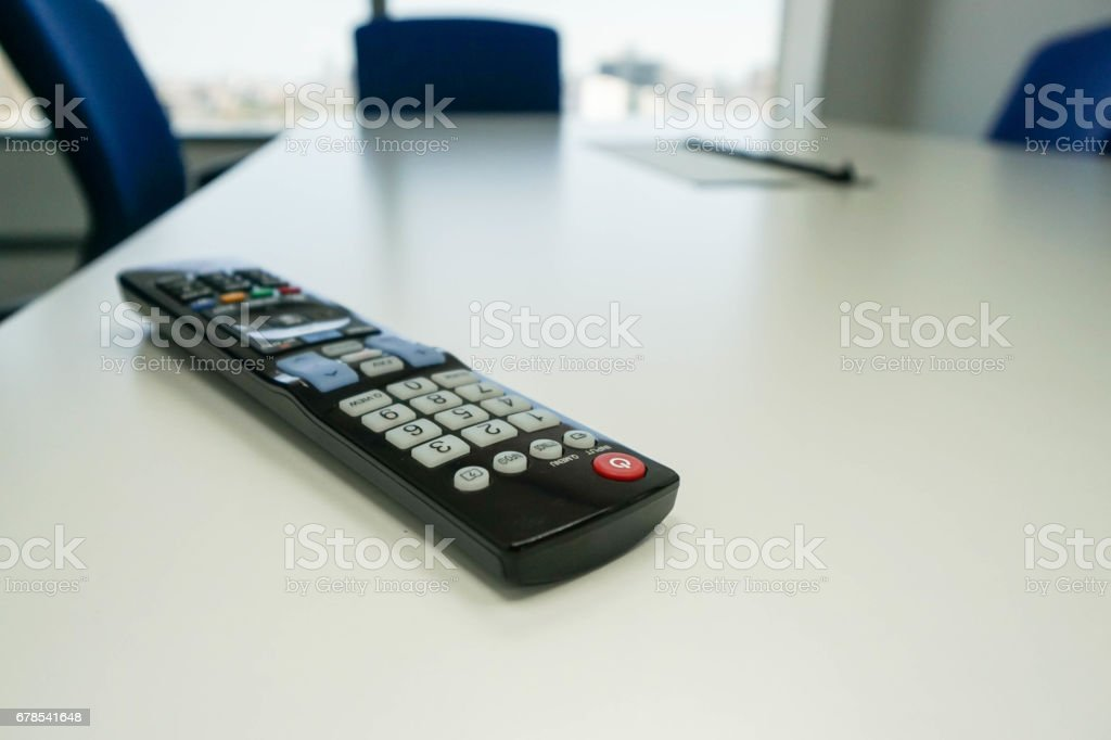 TV remote control in meeting room table with selective focus stock photo