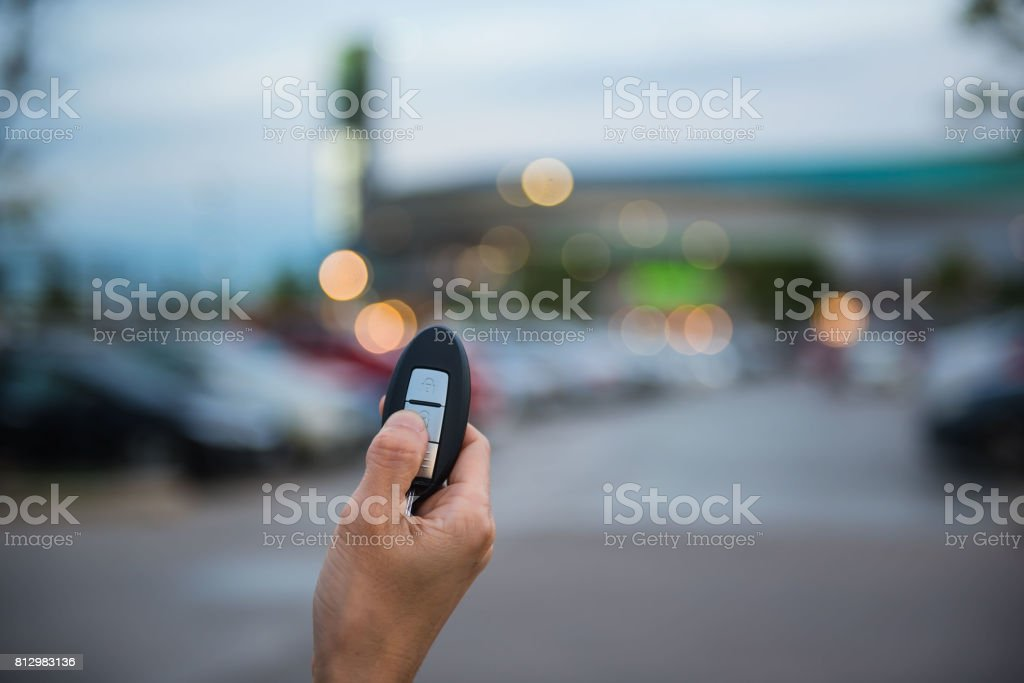remote control  key Car in hand In the outdoor parking lot at evening stock photo