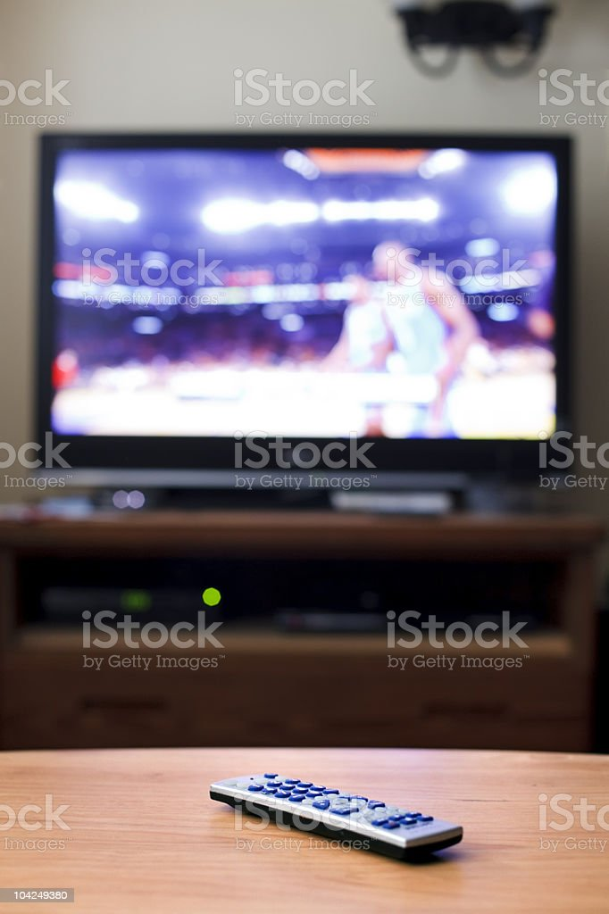Remote control on table with TV showing basketball game stock photo