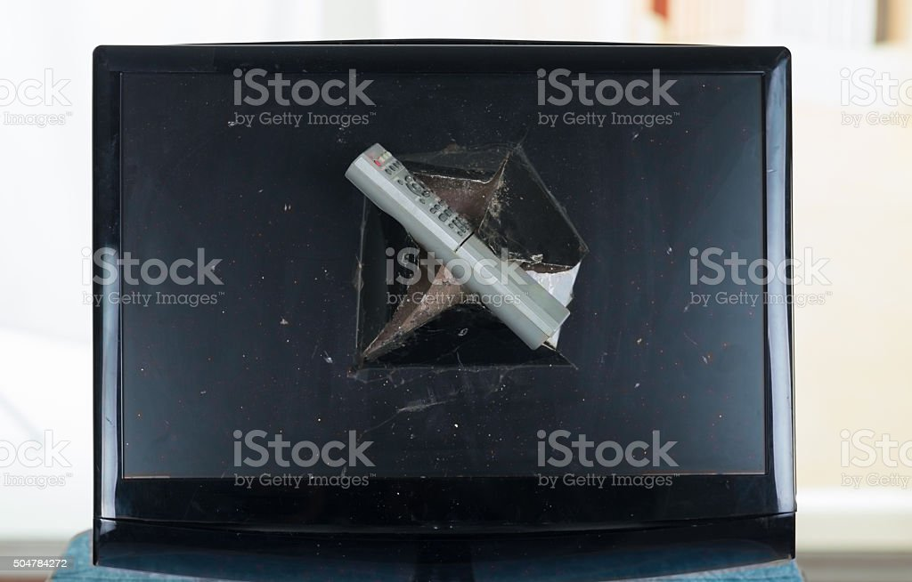 Remote control stuck inside broken computer screen stock photo