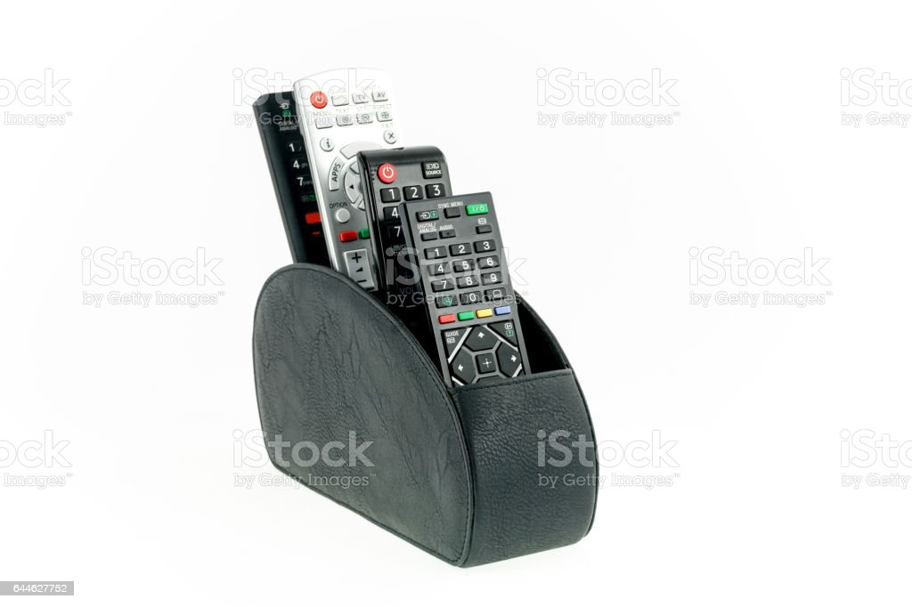 Remote controllers in leather holder isolated on white background stock photo