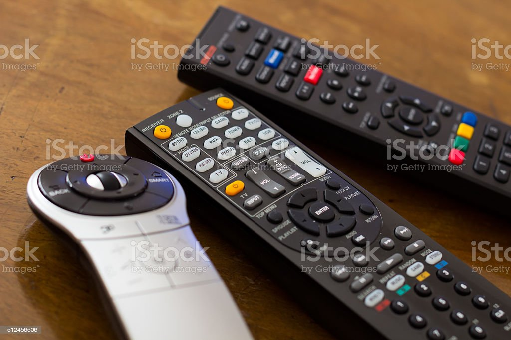 Remote controls on the wooden table stock photo