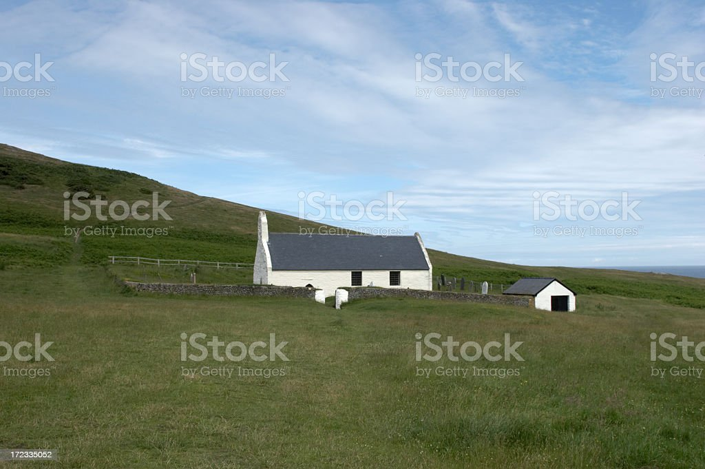 Remote Welsh church on headland fluffy clouds royalty-free stock photo