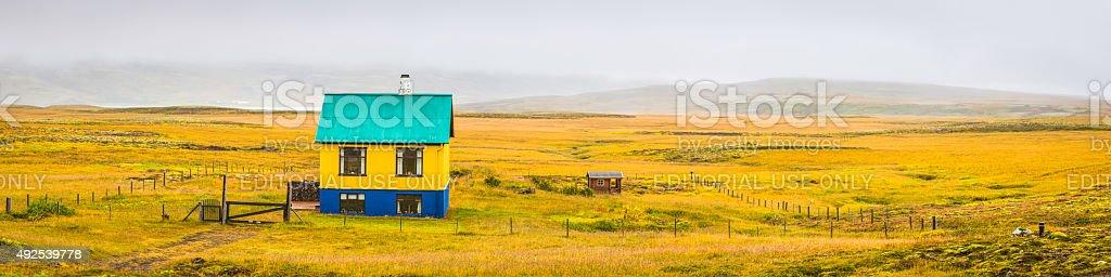 Remote yellow house on wild green grassland panorama Iceland stock photo