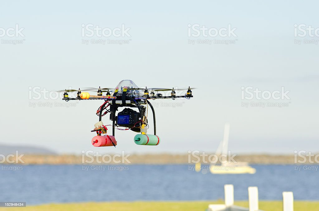 Remote-controlled surveillance helicopter  flying towards yacht carrying camera royalty-free stock photo