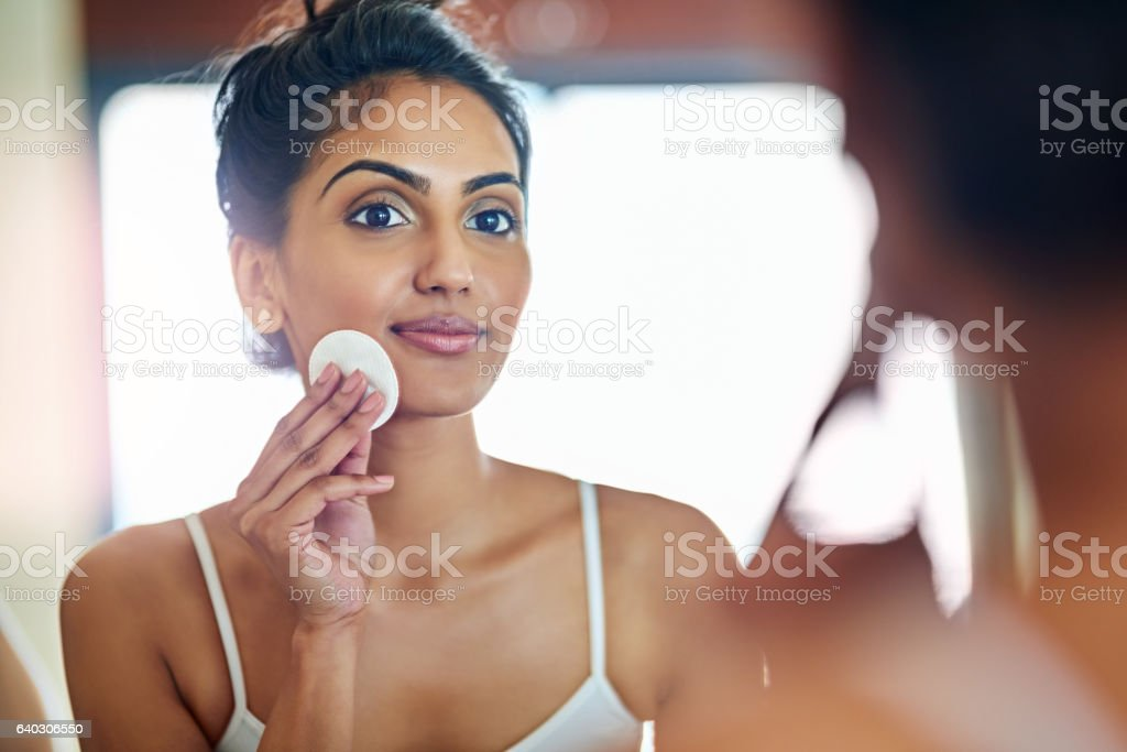 Removing any dirt and buildup on her face stock photo