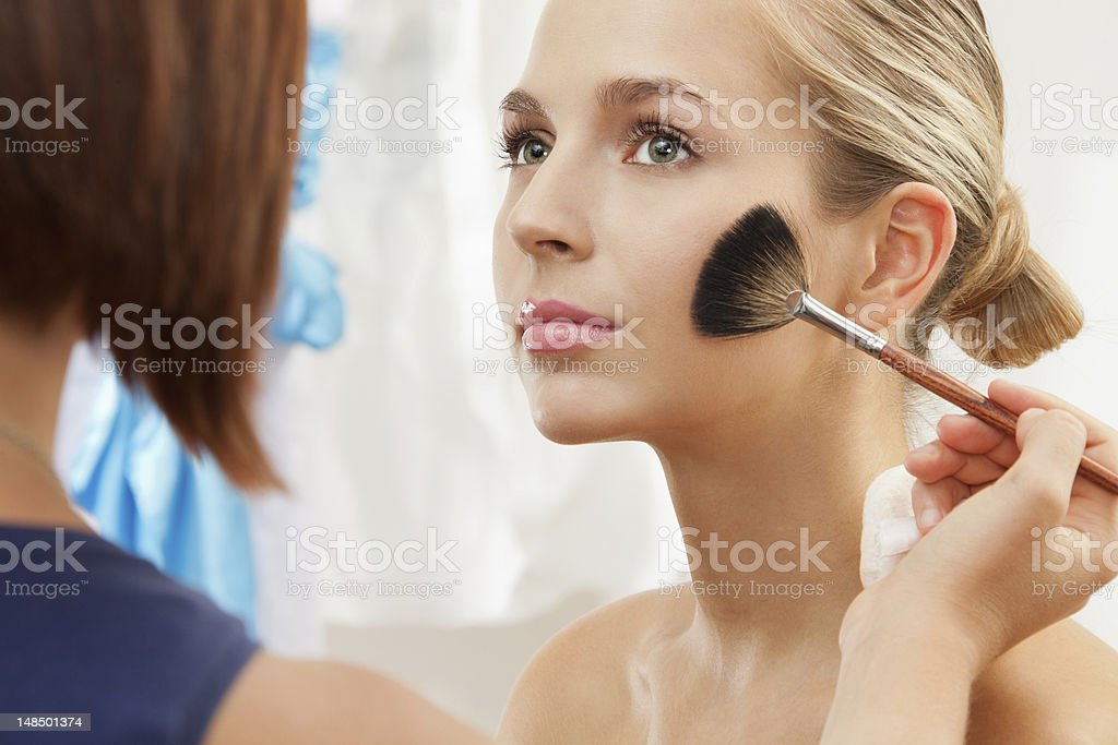 removing excess of powder using fan brush stock photo