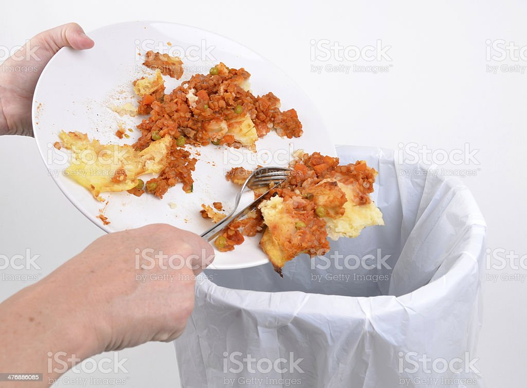 Removing food into a bin stock photo