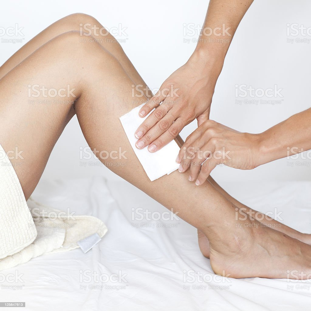 Removing hair from woman's legs stock photo