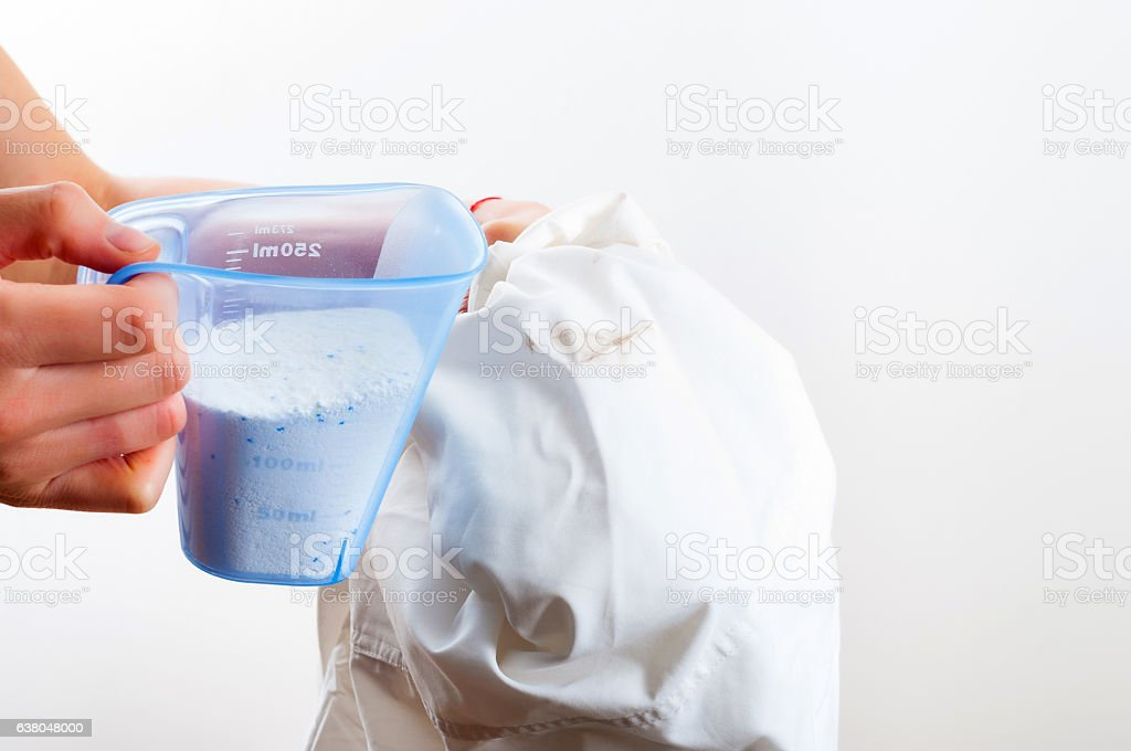 Removing stain from white shirt measuring determent by hand stock photo